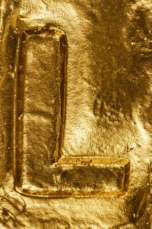 Beautiful handmade letter L on a shiny gold texture Zdjęcie Seryjne