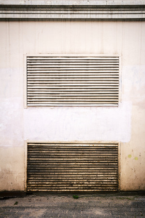 grille': Old steel ventilation grille on the wall of a building