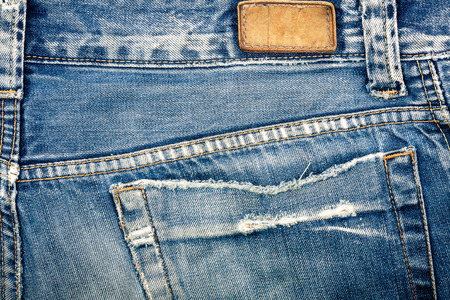 worn jeans: Blank real leather jeans label sewed on old worn blue jeans.