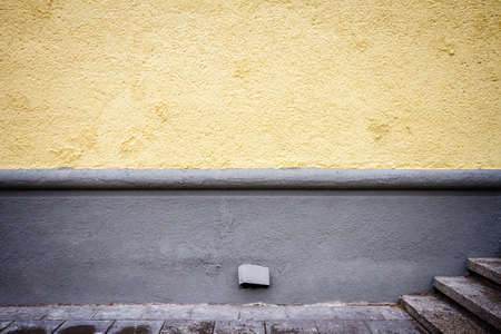 decorative wall: Freshly painted yellow wall, stairs and pavement