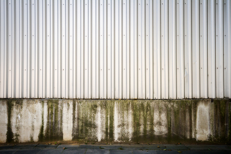 metal base: Gray industrial grooved metal wall on concrete base Stock Photo