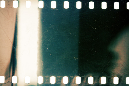Blank grainy film strip texture background with lots of dust, noise and light leak
