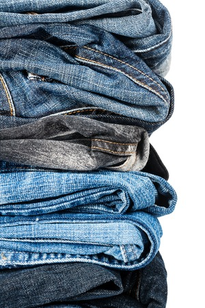 legs folded: Closeup shot of stack of jeans isolated on white background