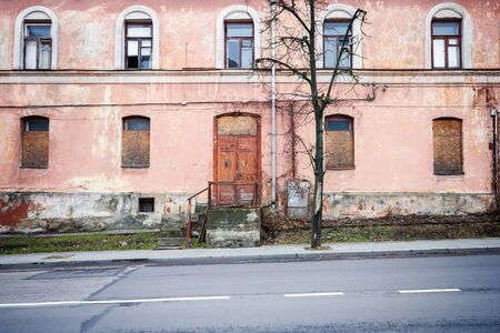 windows and doors: Abandoned weathered pink street wall with some windows and doors