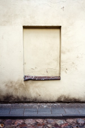 window graffiti: Aged weathered yellow wall with immured window