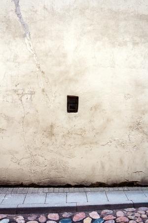 window graffiti: Aged weathered yellow wall with one small window