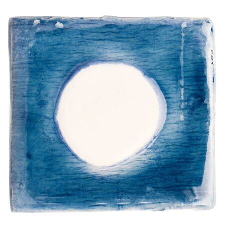 enamel: Blue handmade glazed ceramic tile with big white dot in middle isolated on white