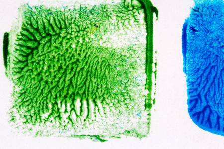 Closeup view of abstract hand painted blue and green acrylic art background on paper texture. Fragment of artwork