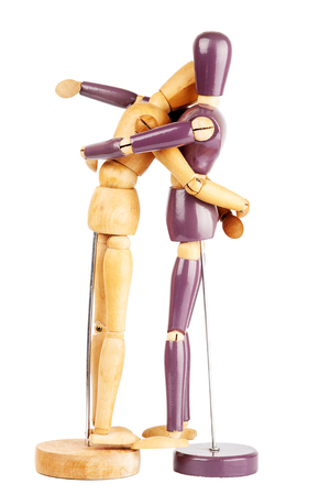 Two wooden dummies hugging each other isolated on a white background