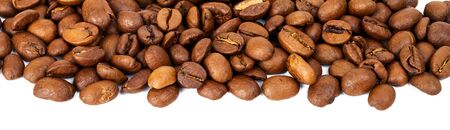 the daily grind: Line of roasted coffee beans isolated in white background, selective focus on the center Stock Photo