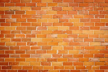 Background of old red and dotted yellow brick wall texture, abstract horizontal architecture wallpaper Stock Photo