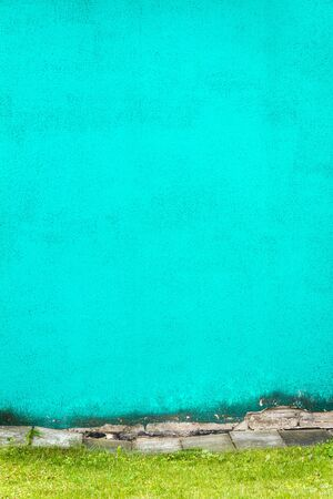 Vibrant cyan plaster wall with green grass