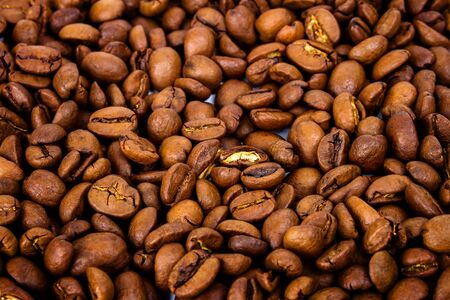 the daily grind: Background of roasted coffee beans, selective focus in the center