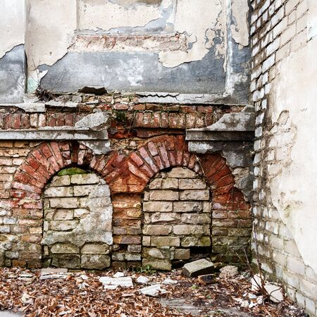 Old abandoned wall with bricked up windows. Architecture detail background. Forgotten building of plaster and red brick Stock Photo