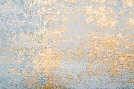 De witte en gouden slordige achtergrond van de muurgipspleistertextuur. Decoratieve muurverf.