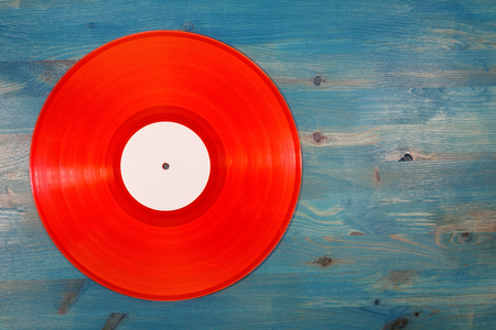 Red transparent vinyl record on blue wooden background Stock Photo