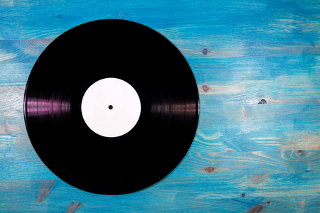 Black color vinyl record with white label on blue wooden background Stock Photo