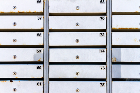 A close up image of rusty old metal mailboxes with numbers Stock Photo