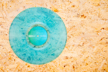 Cyan color transparent vinyl record on plywood background.