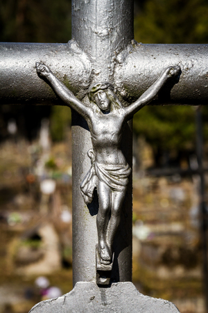 Closeup shot of metal crucifix on a cross in cemetery