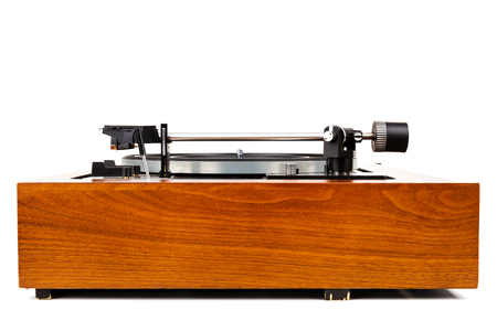 Side view of vintage turntable vinyl record player isolated on white. Wooden plinth. Retro audio equipment. 免版税图像