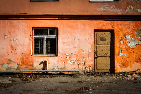 Old orange wall with a window and door. Abandoned building