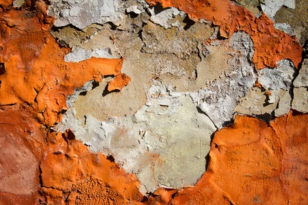 Orange plaster peeling off an old wall. Old dirty peeled plaster wall with falling off flakes of paint. Texture, pattern, background. Banco de Imagens