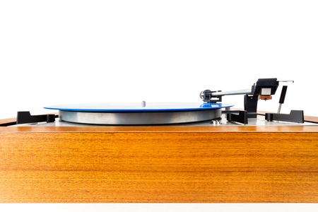 Vintage turntable with a blue vinyl isolated on white. Wooden plinth. Retro audio equipment. 免版税图像