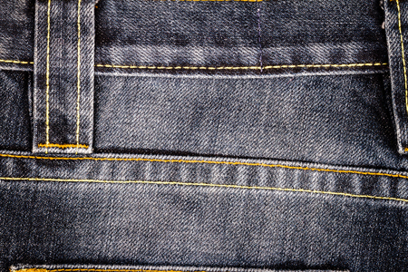 Worn black denim jeans texture with stitches. Abstract jeans texture background