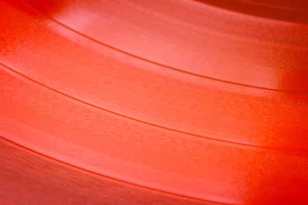 Primo piano della superficie in vinile rosso. Fondo rosso di struttura del disco in vinile. Primo piano del disco LP in vinile che mostra le scanalature
