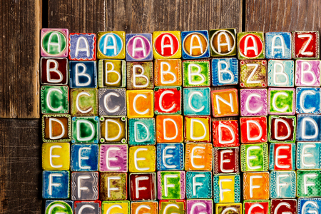 Colorful handmade ceramic alphabet on wood texture