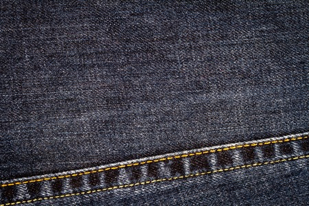 Black jeans texture. Denim jeans fabric background with a seam.