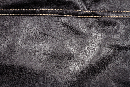 Crumpled black leather texture background. Abstract texture of leather with a seam. Stock Photo