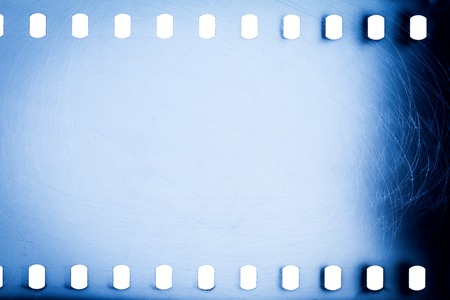 Blank noisy scratched film strip texture background. Blue perforated film isolated on white background.