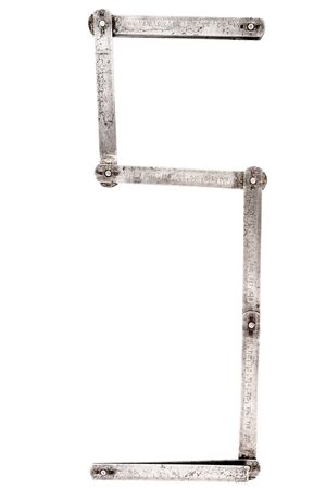 Old iron meter ruler. Old iron folding meter in the shape of letter S isolated on white background. Imagens
