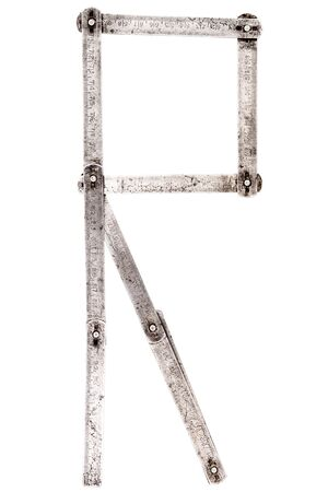 Old iron meter ruler. Old iron folding meter in the shape of letter R isolated on white background. Imagens