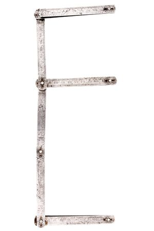 Old iron meter ruler. Old iron folding meter in the shape of letter E isolated on white background.