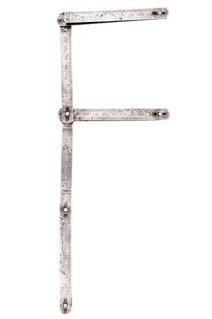 Old iron meter ruler. Old iron folding meter in the shape of letter F isolated on white background. Imagens