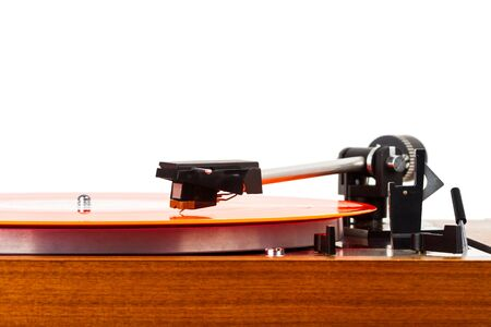 Close up of turntable needle on a vinyl record. Turntable playing music. Stylus on rotating red record.