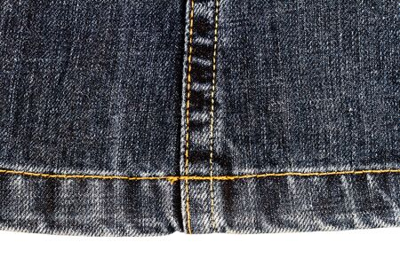 Piece of dark jeans fabric isolated on white background. Rough uneven edges.