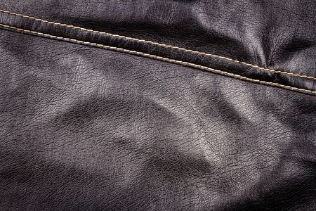 Crumpled black leather texture background. Abstract texture of leather with a seam. Imagens