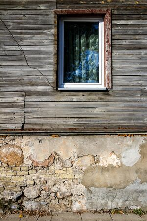 Old window on a aged wooden plank wall. Architectural detail. Architecture background.
