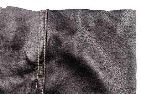 Piece of black leather isolated on white background. Crumpled material texture.