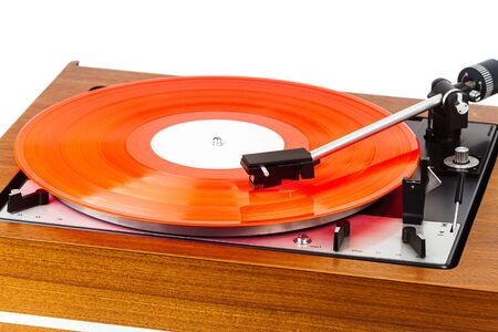 Vintage turntable with a red vinyl isolated on white. Wooden plinth. Retro audio equipment. Imagens