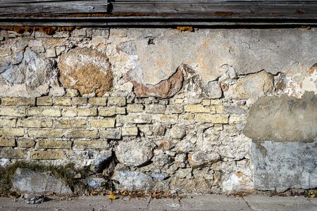 Old gray cracked plaster and brick wall. Abandoned exterior urban background Imagens