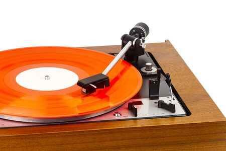Vintage turntable with a red vinyl isolated on white. Wooden plinth. Retro audio equipment. Stock Photo