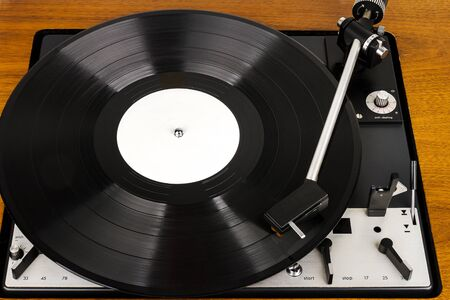 Close up of vintage turntable vinyl record player. Wooden plinth. Retro audio equipment.