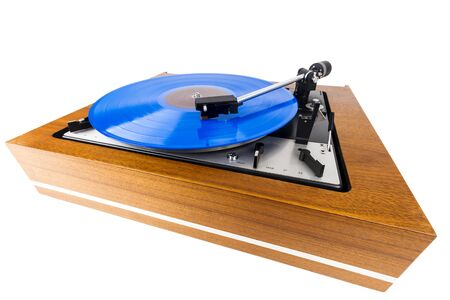 Vintage turntable with a blue vinyl isolated on white. Wooden plinth. Retro audio equipment. Stock Photo
