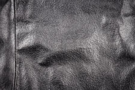 Crumpled black leather texture background. Abstract texture of leather with a seam. Stock Photo - 128822928