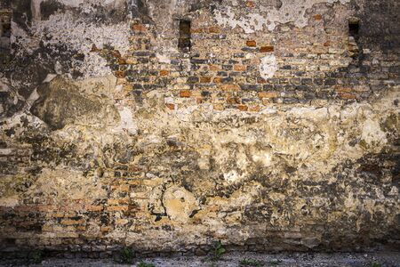 Old gray cracked plaster and brick wall. Abandoned exterior urban background Stock fotó